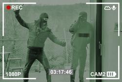 Burglars break the window of a door from the house on surveillance camera
