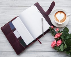 Burgundy leather notebook, pen and cup of coffee  on blackwhite wooden table