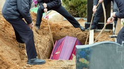 Burial. Men lower the coffin into the grave