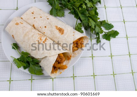 Buritto - traditional Mexican food, on a plate on a blue tablecloth