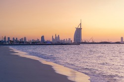 Burj Al Arab in Jumeirah Island or boat building with waves on sea beach, Dubai Downtown skyline, United Arab Emirates or UAE. Financial district in urban city. Skyscrapers at sunset.