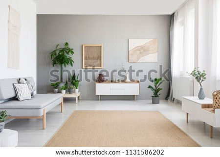 Burlap artwork on grey wall above white cupboard in bright living room interior with sofa and carpet. Real photo #1131586202