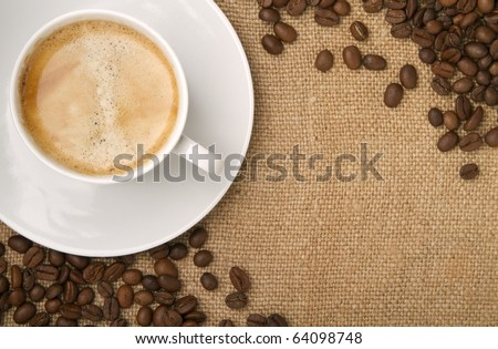 burlap, canvas as a backdrop,  coffee beans as a frame, and a cup of coffee