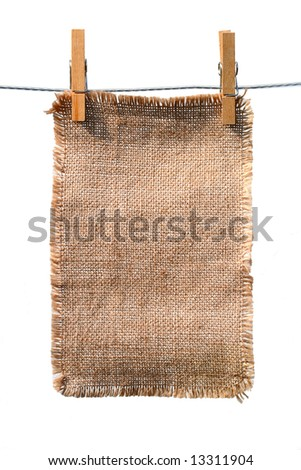 burlap canvas with lacerate edges hanging with wooden pegs, isolated on white