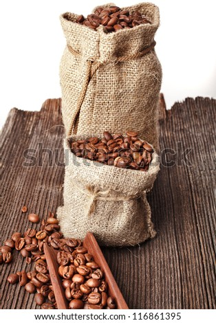 Burlap sack of coffee beans with scoop on white background