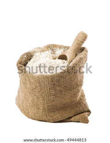 Burlap sack of wholemeal bread flour with wooden scoop on white background