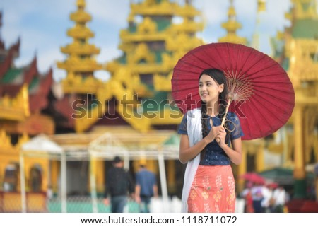Burmese girl holding a red umbrella walking at Shwedagon Pagoda. Young Myanmar girls with Thanaka, a yellowish-white paste made from ground bark and used as a cosmetic and for sunburn.