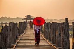 Burmese girl holding a red umbrella walking on U Bein Bridge in the morning in Mandalay, Myanmar.
