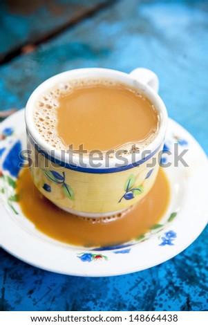 Burmese milk tea on blue wooden table