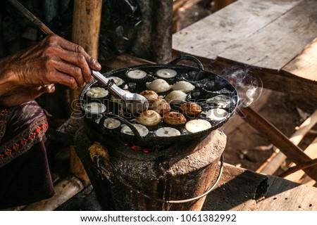 Burmese Woman cooking Mont Lin Ma Yan a traditional Burmese pancake made out of quail egg. Stok fotoğraf ©