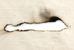 Burn hole on canvas fabric texture and background.