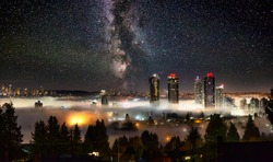 Burnaby, Vancouver, British Columbia, Canada. Beautiful Panoramic Aerial View of a modern city during a fog covered night before winter morning sunrise. Milky Way Galaxy