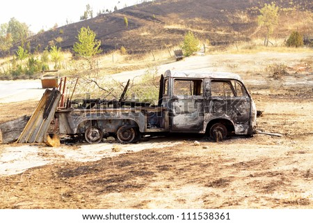 Burned car on desert rural road after forest fire