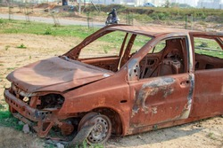 Burned car with burnt paint and empty vehicle at the roadside in wild.