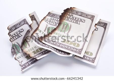 burned dollar bills on white background