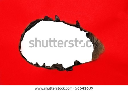 burned hole on a red paper on a white background