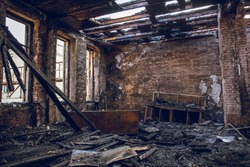 Burned house interior after fire, ruined building room inside, disaster or war aftermath concept