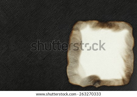 Burned paper put on the black color leather background represent the retro style and vintage paper concept related idea.