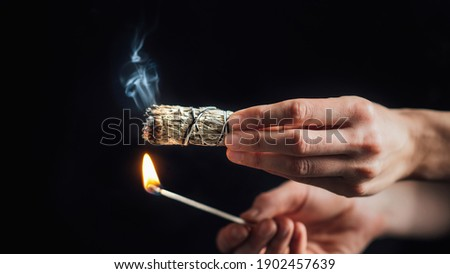 Burning a sage smudge stick for smudging or space cleansing ceremony, black background Stock photo ©