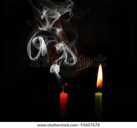 burning and extinguished candles on black background