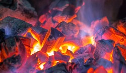Burning and glowing charcoal with open hot flame and smoke close up