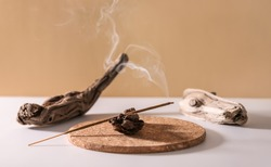 Burning aromatic incense stick for yoga meditation and relaxing on wooden minimalistic background. Aromatherapy smoke.