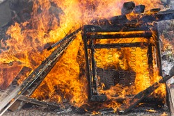 Burning barricade, large armchair burning on bonfire, alight and very hot, polluting disposal of rubbish not environmentally friendly, chair springs visible and wood.