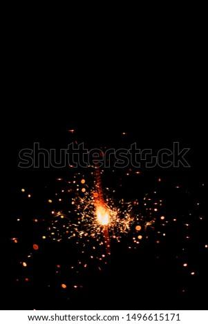 Burning bengal light sparkler on a dark black background. #1496615171