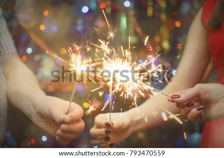 Burning bengal lights in the hands of people family against the background of a Christmas tree. New year celebration. #793470559