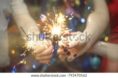 Burning bengal lights in the hands of people family against the background of a Christmas tree. New year celebration. #793470562