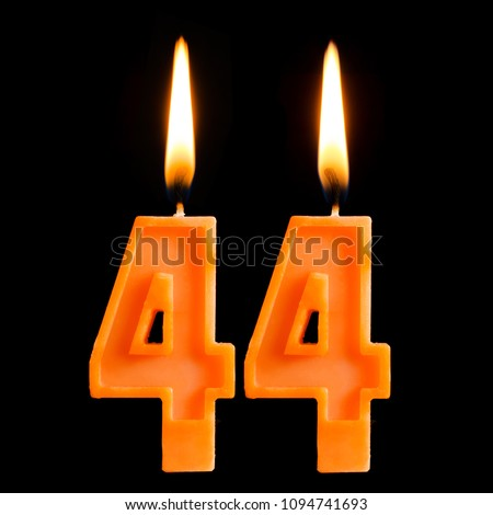 Burning birthday candles in the form of 44 forty four for cake isolated on black background.