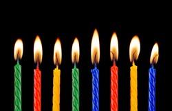 Burning birthday candles on black background.