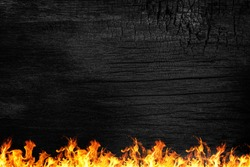 Burning black Board with red fire. Black wooden board and orange flame. Burnt wooden Board texture. Burned scratched hardwood surface. Smoking wood plank background and fire