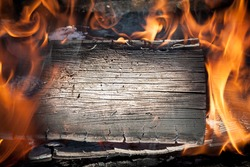 Burning black horizontal board with open red fire flame. Grey burned wooden board texture. Burnt wooden Board. Burned scratched hardwood surface. Smoking wood plank background.
