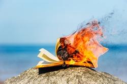 Burning book on the sea coast