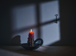 Burning candle against the background of the shadow of the window in the moonlight. A key hangs on the wall. Minimalism. Retro.
