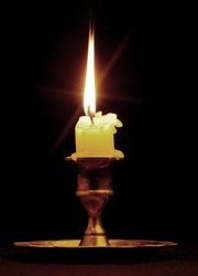 Burning candle. An ancient candlestick, a dark background