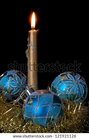 burning candle and blue Christmas balls on a black background