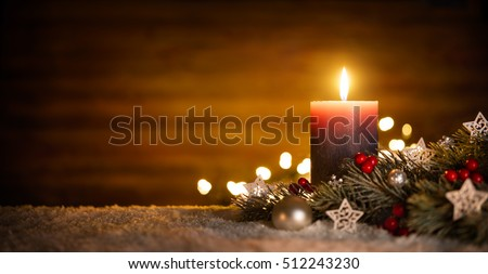 Burning candle and Christmas decoration over snow and wooden background, elegant low-key shot with festive mood #512243230