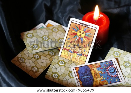 Burning candle and tarot cards-sun and moon