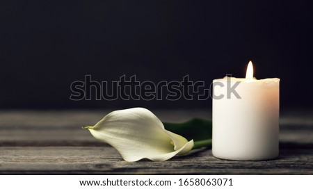 Burning candle and white calla lily on dark background with copy space. Sympathy card   Foto stock ©