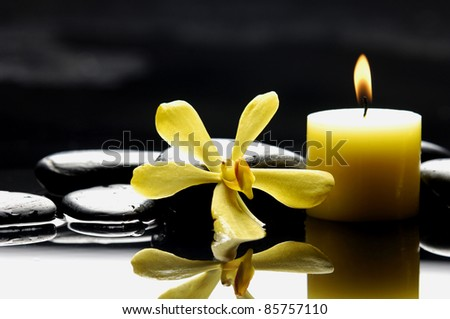 burning candle and yellow orchid on zen stones