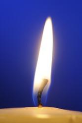 Burning Candle Flame Close-Up on Blue Background