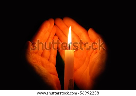 Burning candle in a hand - stock photo