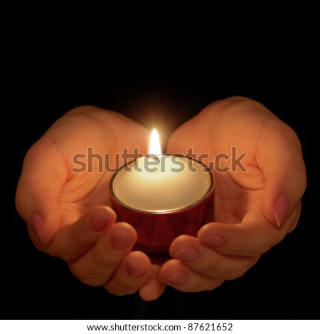 Burning candle in female hands. A black background
