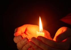 Burning candle in the dark on the hands, coronavirus pandemic, prayer