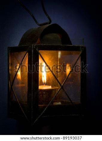 Burning candle inside old dusty lantern, blue background.