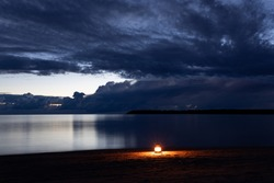 Burning candle lantern on the beach. Sea and storm sky on background. Dramatic clouds. Candle light.
