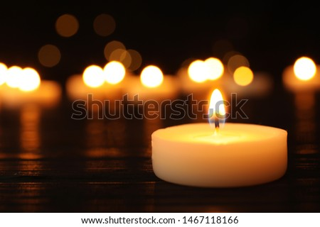 Photo of  Burning candle on black table against blurred background, space for text