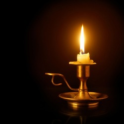 Burning candle on the old brass candlestick over black background